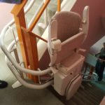 Stairlift at top of stairs going round a bend