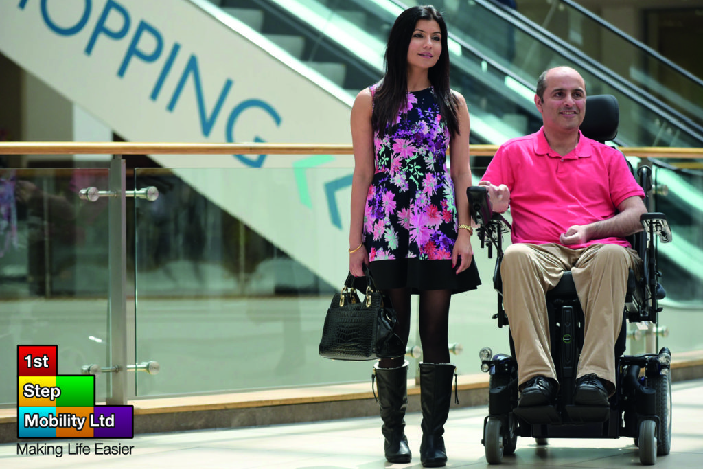 A man using a powerchair from 1st Step Mobility accompanied by a woman