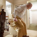 A man about to sit down on his stairlift