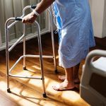 An elderly person holding onto a walking frame.