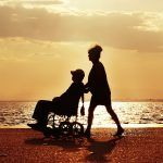 A person pushing another person in a wheelchair by the beach